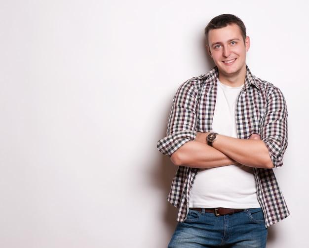 Portrait d'un jeune homme intelligent, debout avec les bras croisés sur fond gris