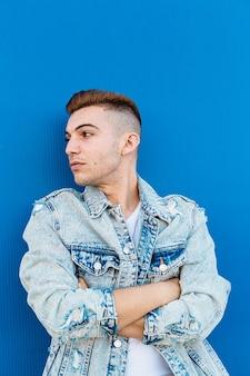 Portrait d'un jeune homme isolé à la confiance et portant une veste en jean dans un bleu