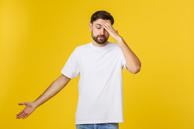 Portrait de jeune homme isolé sur un mur jaune souffrant de maux de tête sévères, pression des doigts sur les tempes, fermeture des yeux pour soulager la douleur