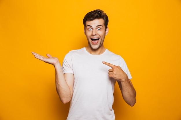 Portrait d'un jeune homme joyeux pointant du doigt loin
