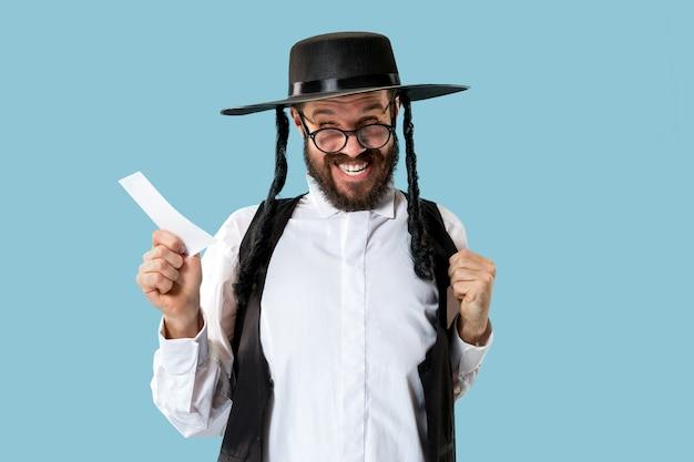Portrait d'un jeune homme juif orthodoxe avec coupon de pari au studio. vacances, célébration, judaïsme, concept de paris.