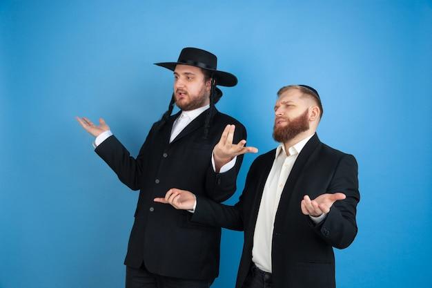 Portrait d'un jeune homme juif orthodoxe isolé sur studio bleu