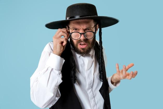 Portrait d'un jeune homme juif orthodoxe pendant le festival de pourim. vacances, célébration, judaïsme, concept de religion. les émotions humaines