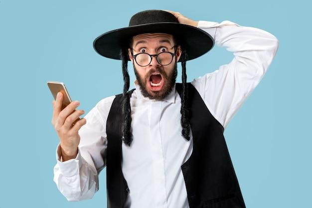 Portrait d'un jeune homme juif orthodoxe avec téléphone portable au studio.