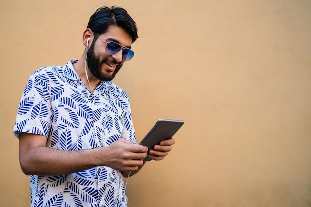 Portrait de jeune homme latin à l'aide de sa tablette numérique avec des écouteurs contre le mur jaune