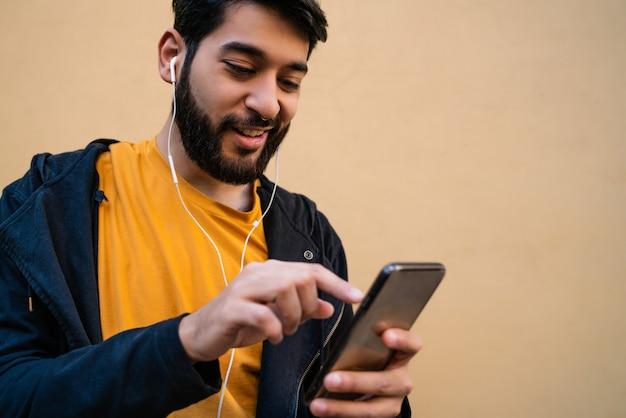 Portrait de jeune homme latin à l'aide de son téléphone portable avec des écouteurs contre jaune