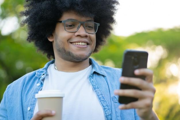 Portrait de jeune homme latin à l'aide de son téléphone portable en se tenant debout à l'extérieur dans la rue