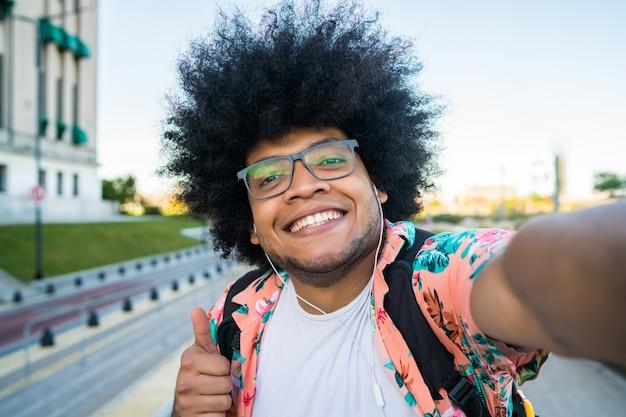 Portrait de jeune homme latin prenant un selfie en se tenant debout à l'extérieur dans la rue
