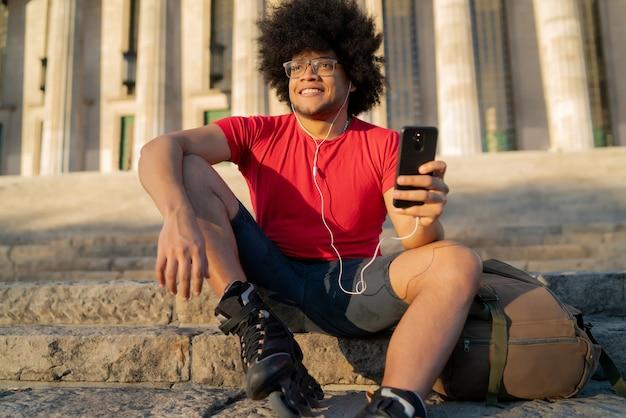 Portrait de jeune homme latin utilisant son téléphone portable et portant des rouleaux de skate alors qu'il était assis à l'extérieur. concept sportif