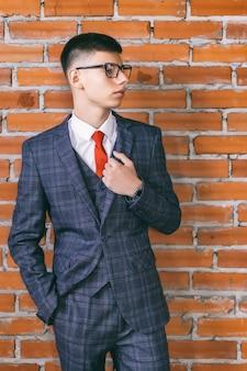 Portrait de jeune homme avec des lunettes en costume d'affaires à la mode, appuyé contre un mur de briques brunes, tonique