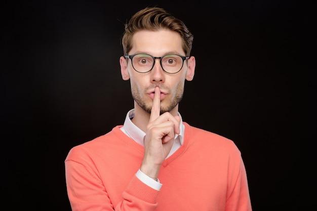 Portrait de jeune homme à lunettes couvrant la bouche avec les mains tout en ne faisant aucun signe de parole, fond isolé