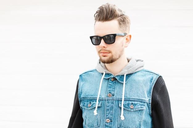 Portrait d'un jeune homme avec des lunettes de soleil et un gilet en jean près du mur