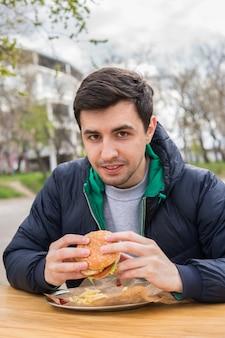 Un portrait de jeune homme mangeant un hamburger