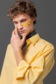 Portrait jeune homme avec maquillage posant
