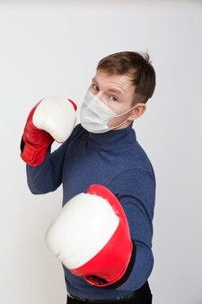 Portrait jeune homme avec masque médical sur son visage en gants de boxe grève gros plan sur fond blanc