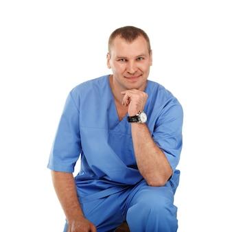Portrait d'un jeune homme médecin dans un uniforme bleu chirurgical médical contre un blanc