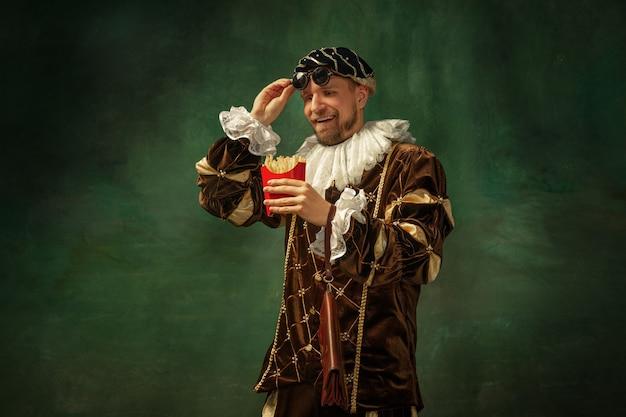 Portrait de jeune homme médiéval en vêtements vintage avec cadre en bois sur un mur sombre, manger des frites