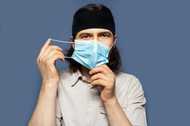 Portrait de jeune homme mettant un masque médical sur le visage contre le coronavirus sur fond de couleur bleue. vue rapprochée de la photo de studio.