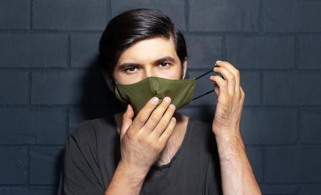 Portrait de jeune homme, mettant un masque respiratoire contre les virus. sur le fond du mur de briques noires.