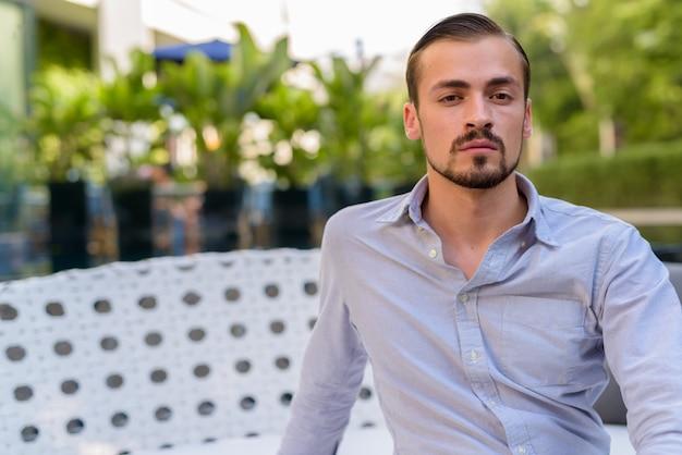 Portrait de jeune homme à la mode barbu assis à l'extérieur