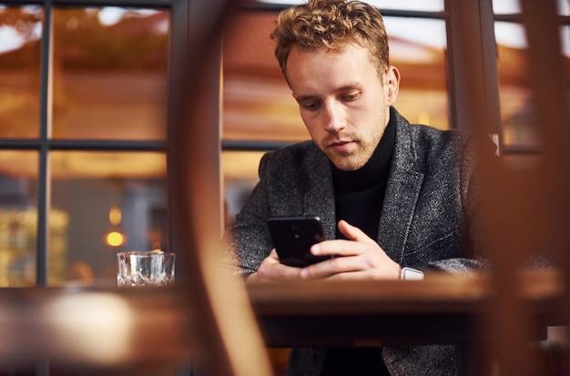 Portrait d'un jeune homme moderne en vêtements formels assis dans le café avec un téléphone dans les mains.