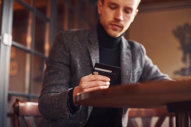 Portrait d'un jeune homme moderne en vêtements formels assis dans le café et tenant une carte de crédit en main.