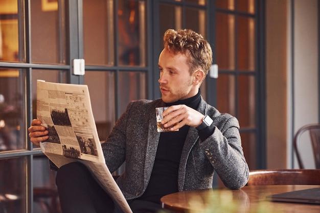 Portrait de jeune homme moderne en vêtements formels qui se trouve dans le café et lit le journal.