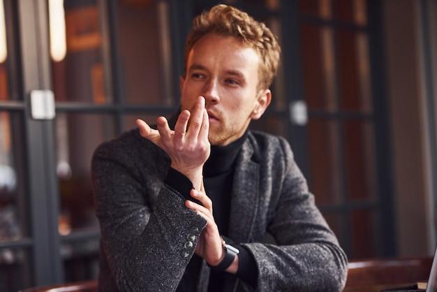 Portrait de jeune homme moderne en vêtements formels qui se trouve dans le café.