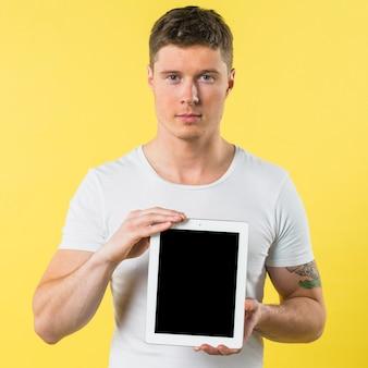 Portrait d'un jeune homme montrant une tablette numérique à écran blanc sur fond jaune