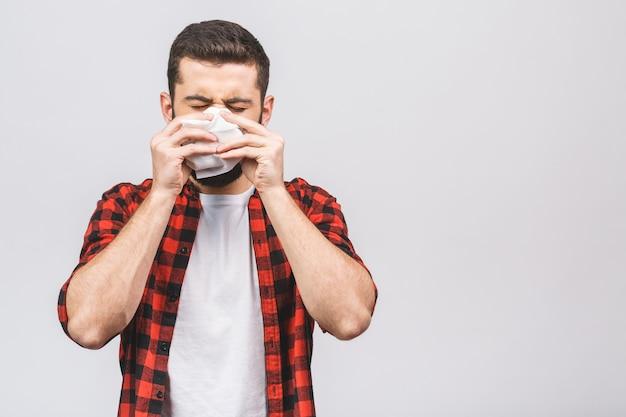 Portrait d'un jeune homme avec un mouchoir. un malade isolé a le nez qui coule. l'homme fait un remède contre le rhume et la grippe.