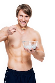 Portrait d'un jeune homme musclé attrayant, manger des flocons avec du lait - isolé sur un mur blanc.