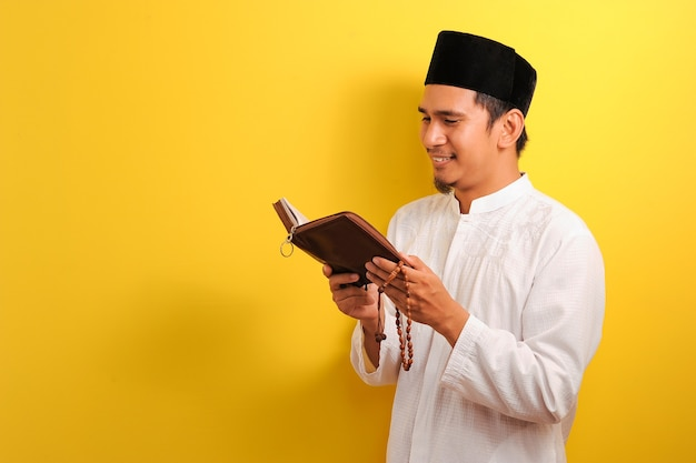 Portrait de jeune homme musulman asiatique lisant le coran sur jaune