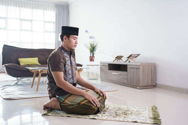 Portrait de jeune homme musulman asiatique priant à la maison
