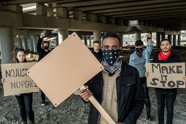 Portrait d'un jeune homme noir brutal et sérieux avec un bandana sur le visage debout avec une bannière contre une équipe d'extrémistes sous le pont