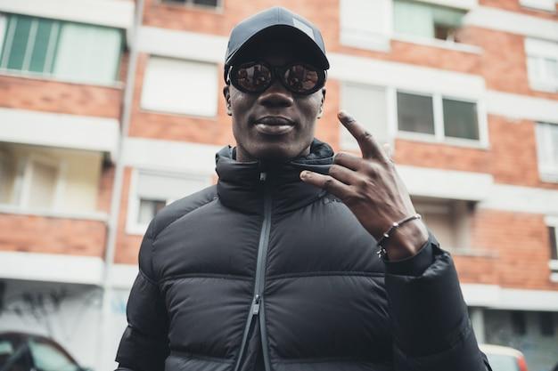 Portrait de jeune homme noir debout geste en plein air avec la main à la recherche de la caméra