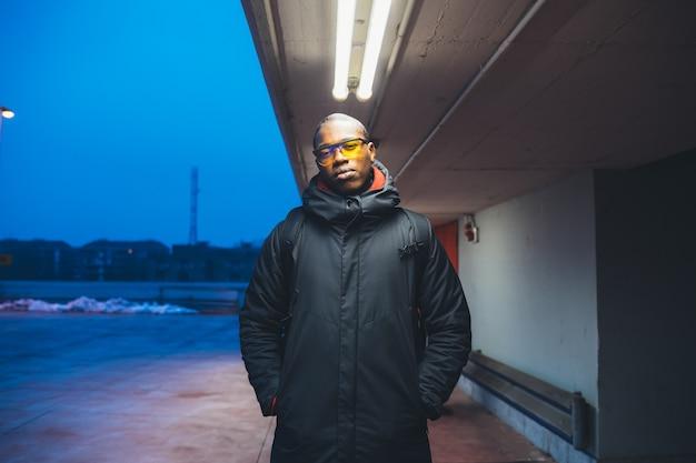 Portrait de jeune homme noir à la recherche de caméra et pose en plein air