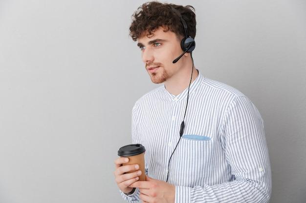 Portrait d'un jeune homme opérateur téléphonique magnifique portant un casque de microphone et tenant une tasse de café tout en parlant avec un client isolé sur un mur gris