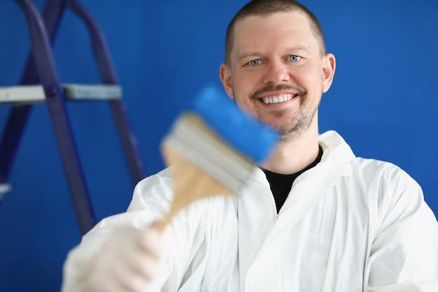 Portrait de jeune homme ouvrier du bâtiment en tenue de protection avec pinceau et peinture