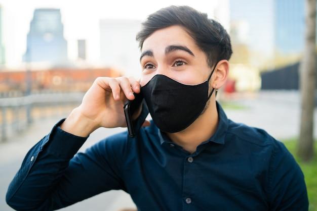 Portrait de jeune homme parlant au téléphone alors qu'il était assis sur un banc à l'extérieur. nouveau concept de mode de vie normal.