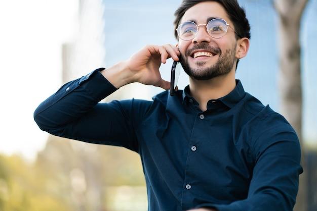 Portrait de jeune homme parlant au téléphone tout en se tenant à l'extérieur