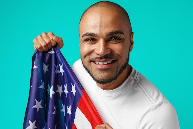Portrait de jeune homme à la peau sombre tenant fièrement le drapeau des usa