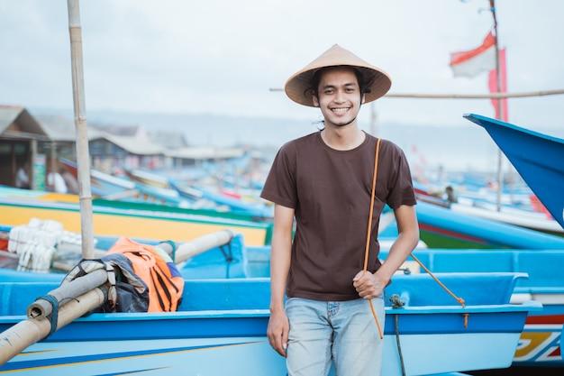 Portrait d'un jeune homme pêcheur appuyé sur un bateau avant de pêcher