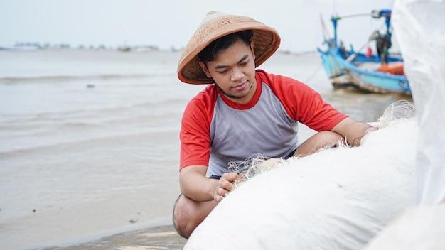 Portrait d'un jeune homme pêcheur préparant un filet de pêche à la plage