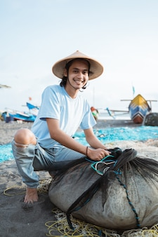 Portrait d'un jeune homme pêcheur préparant un filet de pêche