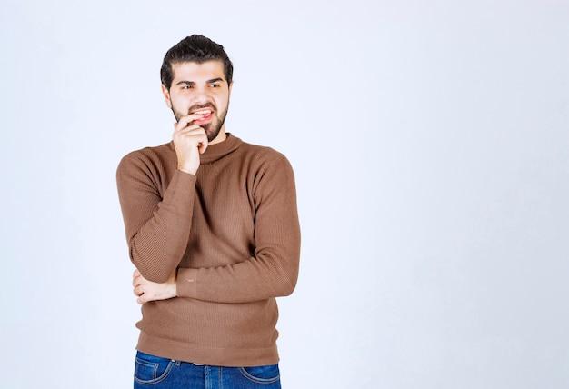 Portrait d'un jeune homme pensant et debout contre un mur blanc.
