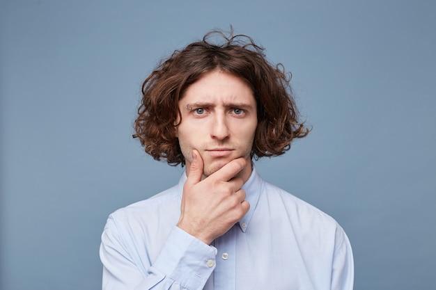 Portrait d'un jeune homme pensive habillé en chemise tenant la main sur son menton isolé sur bleu