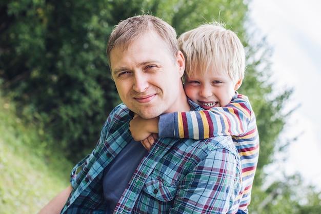 Portrait d'un jeune homme et d'un petit garçon serrant leur père sur une pelouse d'été le jour de l'été. fête des pères, bonne paternité