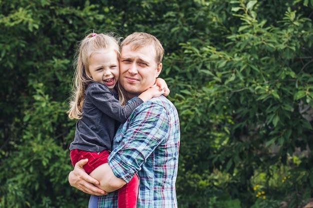 Portrait d'un jeune homme et d'une petite fille étreignant son père sur une pelouse d'été par une chaude journée d'été, paternité heureuse
