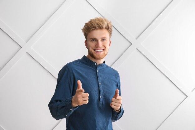 Portrait de jeune homme pointant vers le spectateur