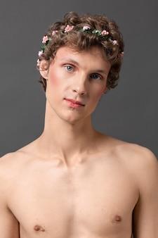 Portrait jeune homme portant maquillage et couronne de fleurs